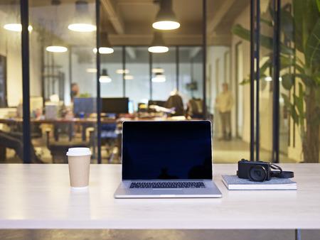 Laptop, Kamera, Kaffee auf einem Tisch in einem modernen, stilvollen Büro eines kleinen Unternehmens.