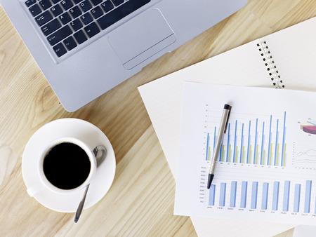 pensamiento estrategico: vista aérea de escritorio de un hombre de negocios con café, ordenador portátil, lápiz y los informes impresos.
