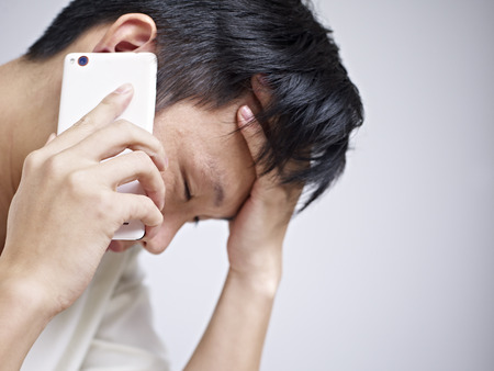 disheartened: asian young man looking sad and depressed while talking on cellphone.