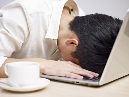 asian man: frustrated asian young man buries his head in the keyboard of a laptop computer.