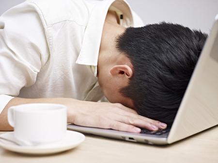 teclado: joven asi�tico frustrado entierra su cabeza en el teclado de un ordenador port�til. Foto de archivo