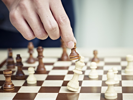 strategic focus: hand picking up a pawn attacking opponent Stock Photo