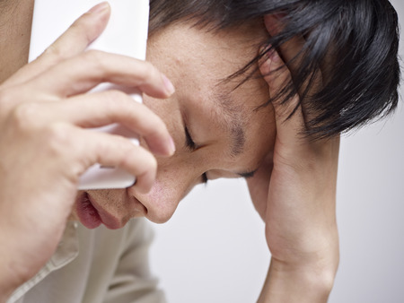 close-up of an asian young man looking sad and depressed while talking on cellphone. photo