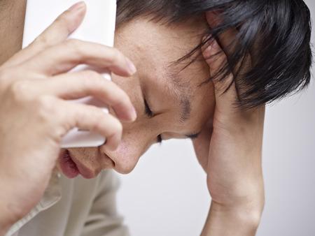 jornada de trabajo: primer plano de un joven asiático de mirada triste y deprimido mientras se habla por teléfono celular.