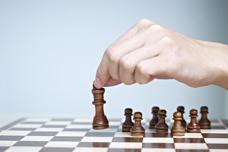 playing chess: hand picking up and moving a chess piece.