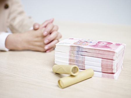 rmb: woman sitting at a table with a stack of Renminbi (RMB, chinese yuan).