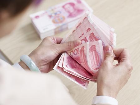 contando dinero: primer plano de las manos de una joven cajera de banco contando dinero. Foto de archivo