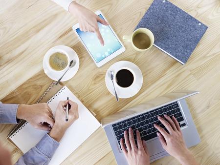 cenital: tres ejecutivos de negocios sentados alrededor de la reunión de escritorio que tiene, con café, portátil y tablet PC y portátiles, vista aérea.