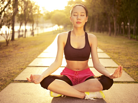 meditating woman: young and beautiful asian woman practicing yoga outdoors in park in the warm light of sunset, meditation, fitness, healthy life and lifestyle concept. Stock Photo