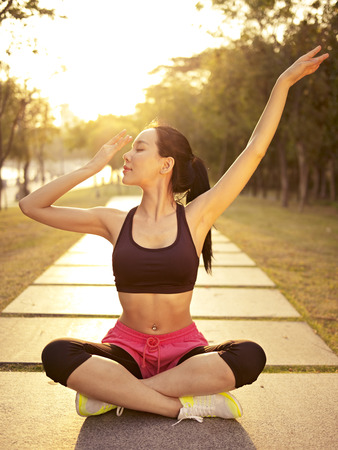young and beautiful asian woman practicing yoga outdoors in park in the warm light of sunset, meditation, fitness, heathy life and lifestyle concept. photo