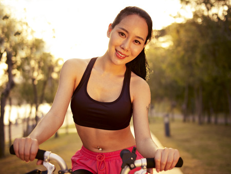 east riding: young and beautiful asian woman riding bicycle outddors in park at sunset, smiling and cheerful, fitness, sport and exercise, healthy life and lifestyle concept.