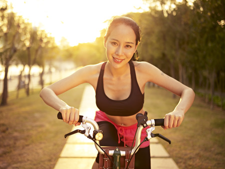 korea girl: young and beautiful asian woman riding bicycle outdoors in park at sunset, smiling and cheerful, fitness, sport and exercise, healthy life and lifestyle concept. Stock Photo