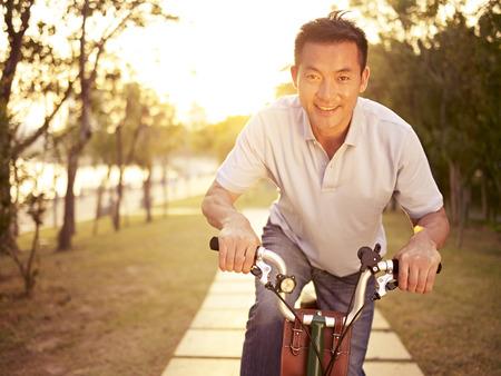medio volwassen Aziatische man rijden fiets buiten bij zonsondergang, lachend en gelukkig, fitness, sport en bewegen, gezond leven en lifestyle concept.