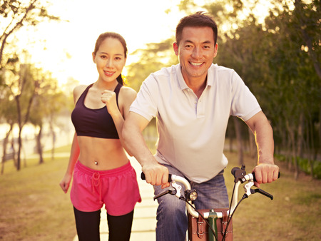 asia: young asian couple running, riding bike outdoors in park at sunset, fitness, sport and exercise, healthy life and lifestyle concept.