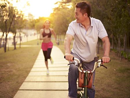 ライフスタイル: 若いアジアのカップルを実行して、自転車に乗って公園夕日、フィットネス、屋外でスポーツ、運動、健康的な生活とライフ スタイルのコンセプト。