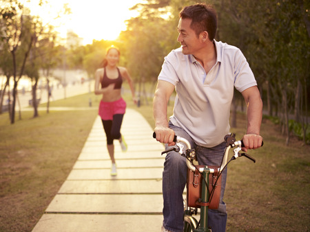 exercises: young asian couple running, riding bike outdoors in park at sunset, fitness, sport and exercise, healthy life and lifestyle concept.
