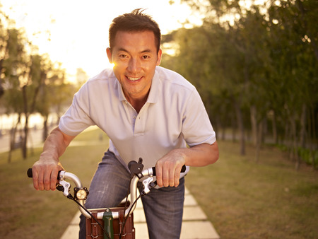 mid-adult asian man riding bicycle outdoors at sunset, smiling and happy, fitness, sport and exercise, healthy life and lifestyle concept.