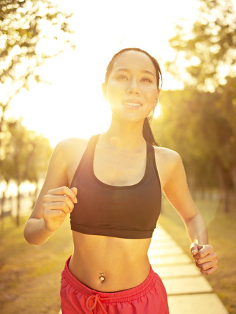 run out: young and fit asian woman running jogging outdoors in park at sunset, fitness, sport and exercise, healthy life and lifestyle concept.