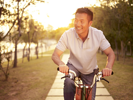 mid morning: mid-adult asian man riding bicycle outdoors at sunset, smiling and happy, fitness, sport and exercise, healthy life and lifestyle concept.