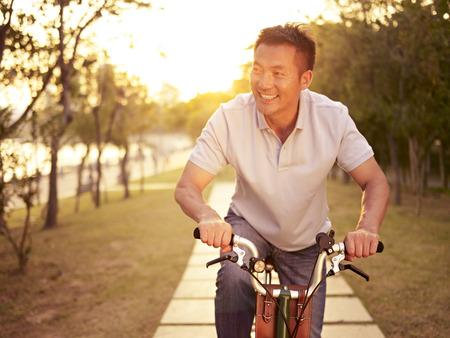 Mitte erwachsenen asiatischen Mann Fahrradfahren im Freien bei Sonnenuntergang, lächelnd und glücklich, Fitness, Sport und Bewegung, gesundes Leben und Lifestyle-Konzept. Standard-Bild