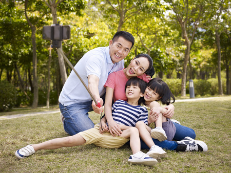 to stick: happy asian family with two children taking a outdoor selfie with selfie stick outdoors in a city park.