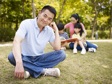 two generation family: asian father sitting on grass happy and content with wife taking care of children in the background.
