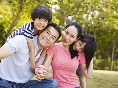 gia đình châu Á với hai trẻ em chụp ảnh gia đình ở ngoài trời trong một công viên thành phố.