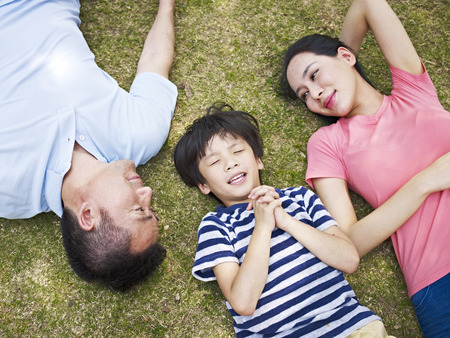 little asian boy lying on grass making a wish with eyes closed while his parents looking at him affectionately.