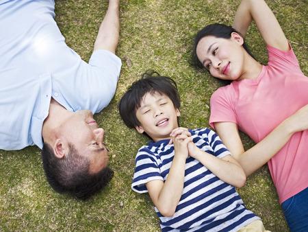 小さなアジアの少年は目を閉じて彼の両親は、愛情を込めて彼を見ている間願いを作る草の上に横たわる。