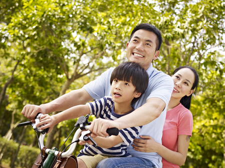 family on grass: mother father and son riding a bicycle together outdoors in a city park. Stock Photo