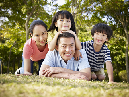 the photo: happy asian family with two children taking a family photo outdoors in a park.