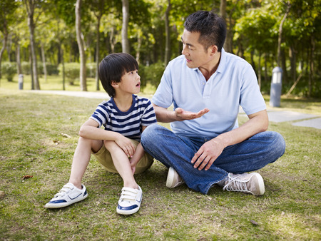 asian father and elementary-age son sitting on grass outdoors having a serious conversation. Archivio Fotografico