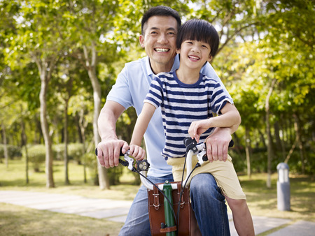 asian father and elementary-age son enjoying riding a bike outdoors in a park. Stockfoto