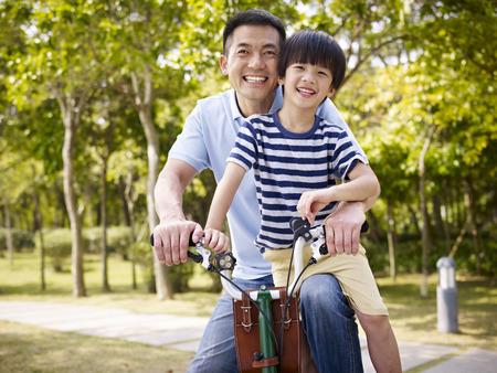 padre asiático e hijo en edad elemental enjoying andar en bicicleta al aire libre en un parque.
