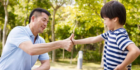 family with one child: asian father and elementary-age son sealing a deal or promise outdoors in a park. Stock Photo