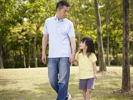 padres hablando con hijos: padre asi�tico e hija en edad de primaria disfrutando de un paseo en la naturaleza. Foto de archivo