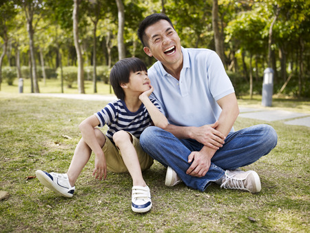 asian father and elementary-age son sitting on grass outdoors having an interesting conversation.