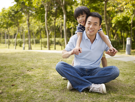 asian father and elementary-age son enjoying outdoor activity in park.