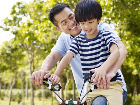 ni�os en bicicleta: padre asi�tico e hijo en edad elemental enjoying andar en bicicleta al aire libre en un parque.