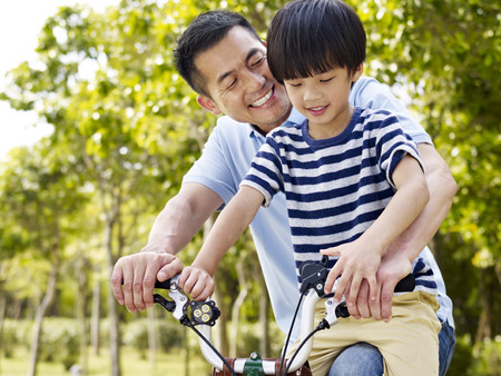 asian father and elementary-age son enjoying riding a bike outdoors in a park. Archivio Fotografico