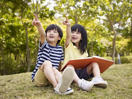小さなアジアの少年と空を指している草の上に座って手に本を持つ少女。