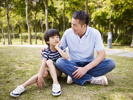 asian father and elementary-age son sitting on grass outdoors having a conversation.