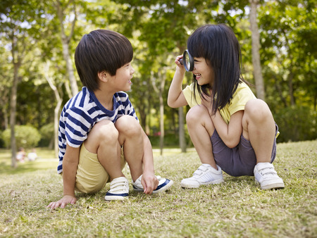 ni�as peque�as: ni�a asi�tica mirando peque�o muchacho asi�tico a trav�s de una lupa al aire libre en un parque. Foto de archivo