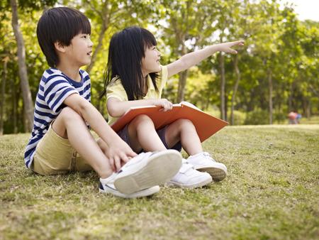 ni�as chinas: peque�o muchacho asi�tico y ni�a con el libro en la mano sentado en la hierba que apunta a la distancia Foto de archivo