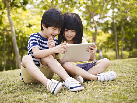 little asian girl and boy sitting on grass using digital tablet outdoors in a park.