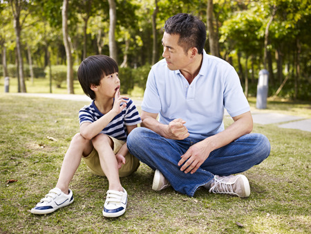 ni�os hablando: padre asi�tico e hijo en edad de primaria sentados en el c�sped al aire libre que tiene una conversaci�n. Foto de archivo