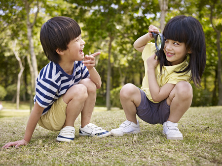 magnify: little asian girl looking at little asian boy through a magnifier outdoors in a park. Stock Photo