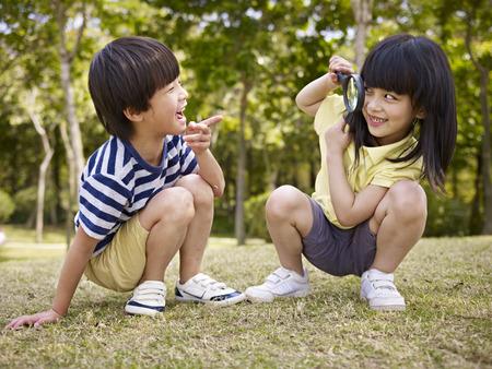 brothers playing: ni�a asi�tica mirando peque�o muchacho asi�tico a trav�s de una lupa al aire libre en un parque. Foto de archivo