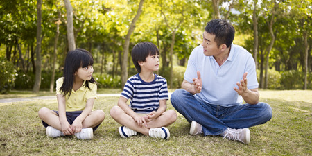 asian father and two children sitting on grass having an interesting conversation, outdoors in a park. Imagens
