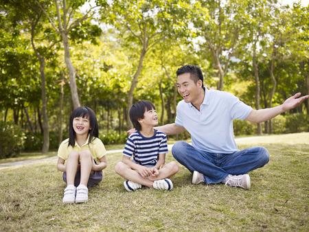 ni�os chinos: padre asi�tico y dos ni�os sentados en la hierba que tiene una conversaci�n interesante, al aire libre en un parque. Foto de archivo